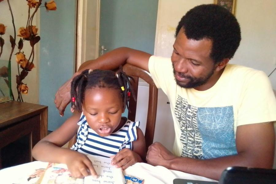 Mazunzo listens as his five-year-old daughter Mathando reads