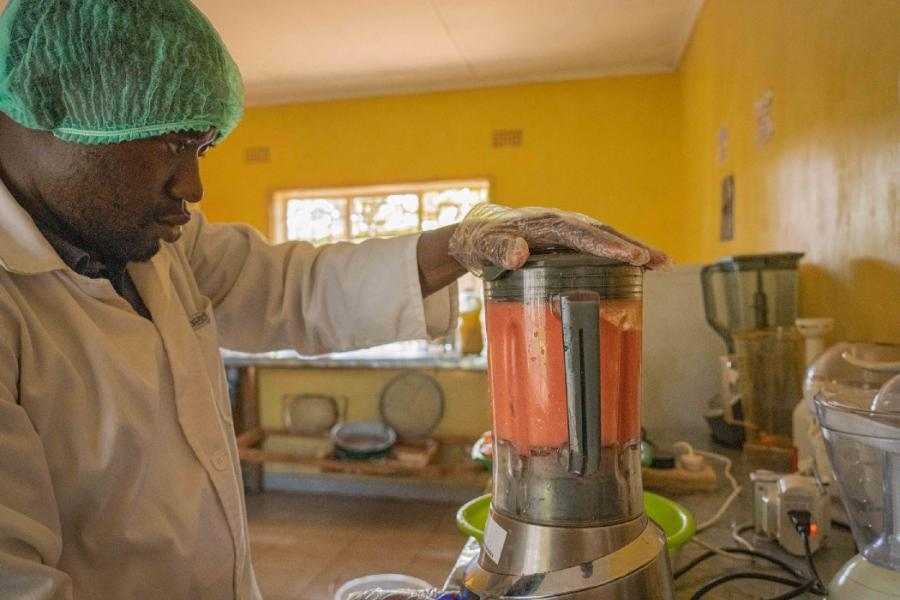 Mtisunge processes nutritious fresh juice for pregnant women in his community. Photo: WFP/Francis Thawani